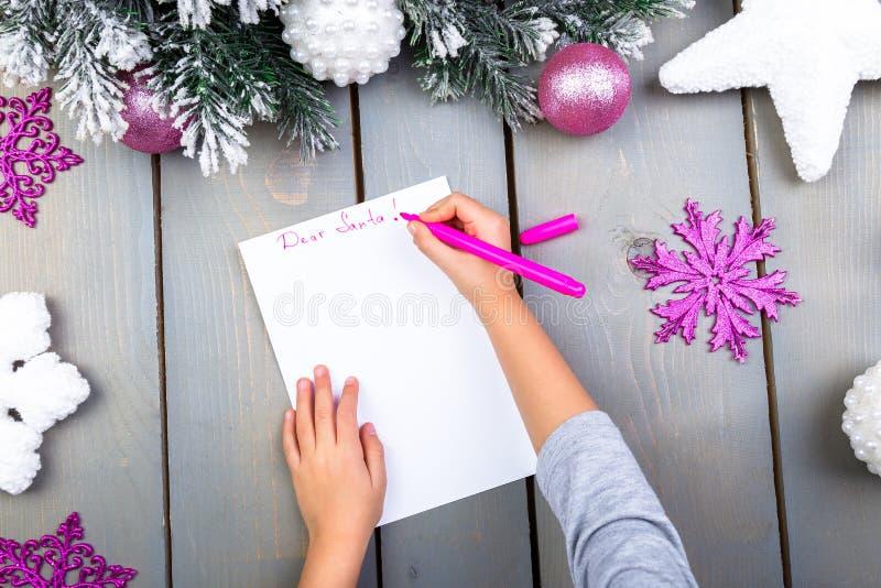 El niño escribe la letra a Santa Claus Manos del niño Visión superior foto de archivo libre de regalías