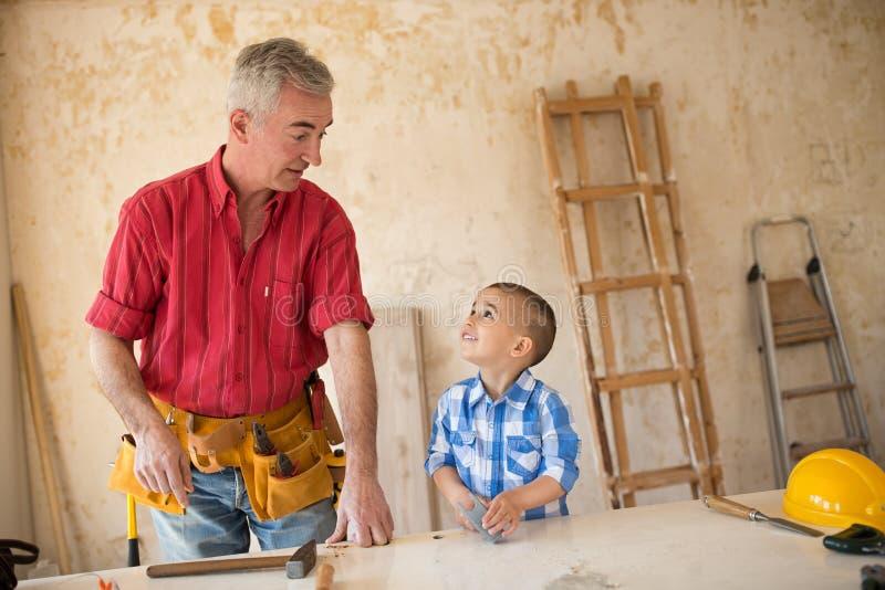 El niño está ayudando a su abuelo en el taller imagenes de archivo