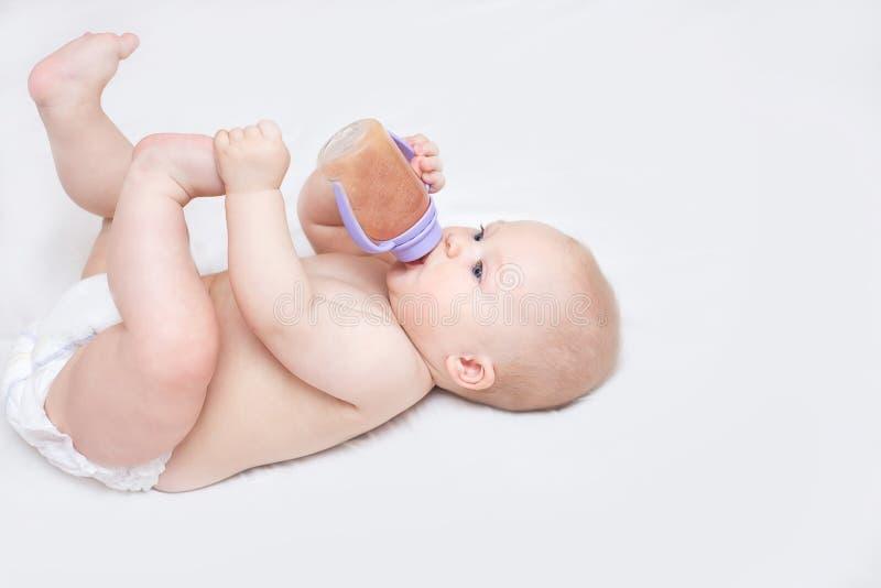 El niño está bebiendo de una botella y de una mentira foto de archivo