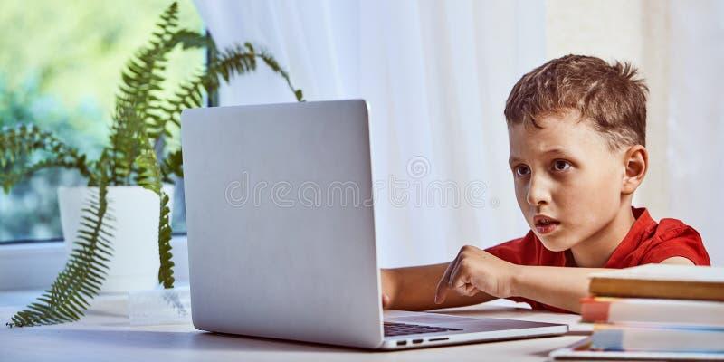 El niño está buscando la información sobre Internet a través de un ordenador portátil uno mismo-estudio en casa, haciendo la prep imagen de archivo