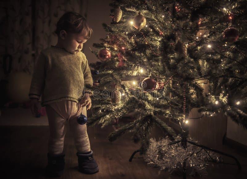 El niño está colgando la decoración en el árbol de navidad foto de archivo