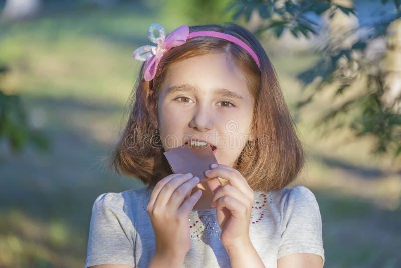 El niño está comiendo el chocolate foto de archivo