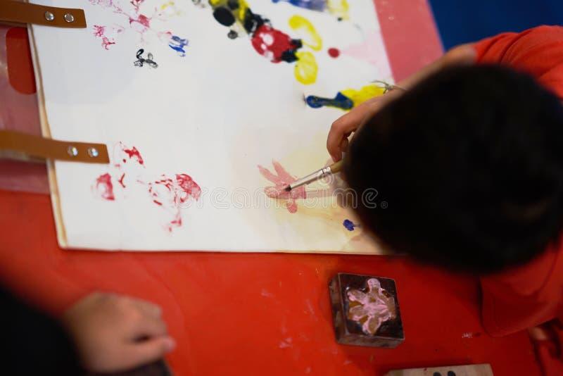 El niño está dibujando las ilustraciones coloreando, visión superior foto de archivo libre de regalías