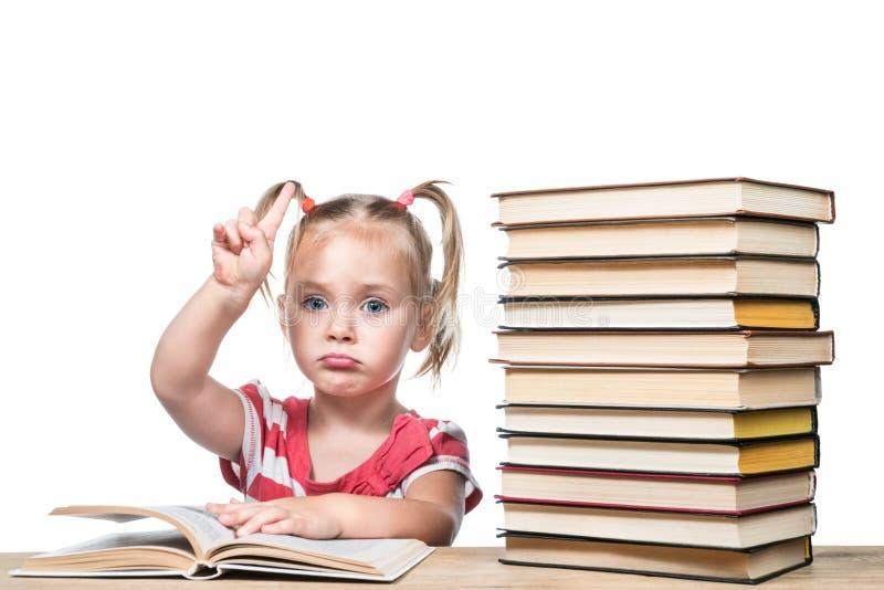 El niño está estudiando el libro foto de archivo