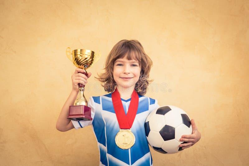El niño está fingiendo ser jugador de fútbol imagenes de archivo