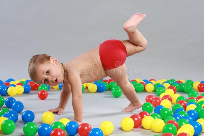 El niño está jugando con las bolas coloreadas imagen de archivo