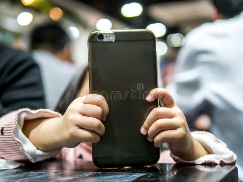 El niño está jugando con el teléfono móvil foto de archivo libre de regalías