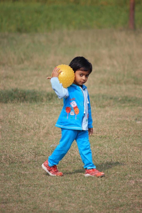 El niño está jugando con una bola amarilla foto de archivo libre de regalías