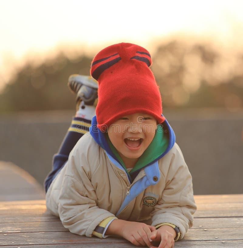 El niño está jugando en la puesta del sol fotografía de archivo libre de regalías