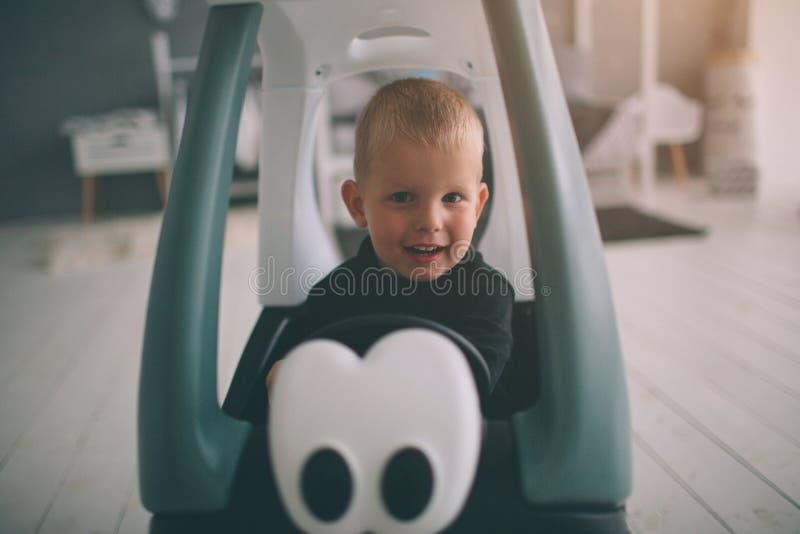 El niño está poniendo en el piso El muchacho está jugando en hogar con los coches del juguete en casa por la mañana Forma de vida foto de archivo