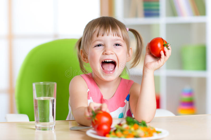 El niño feliz come la cena y muestra los tomates fotografía de archivo libre de regalías