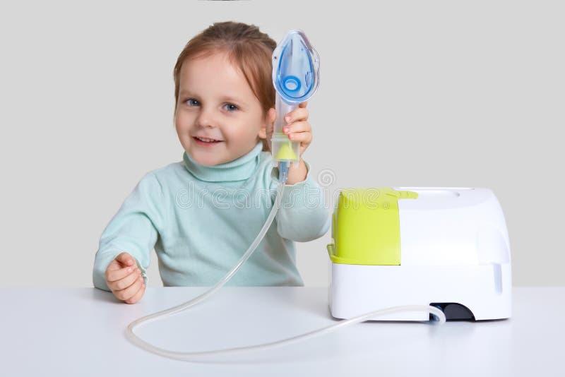 El niño feliz con aspecto europeo hace la inhalación en casa, las curaciones tose, tiene frío o la gripe, muestra que la máscara  imagenes de archivo