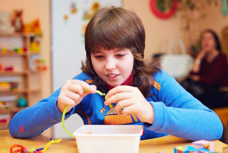 El niño feliz con incapacidad desarrolla capacidades finas de motor en el centro de rehabilitación para los niños con necesidades fotos de archivo