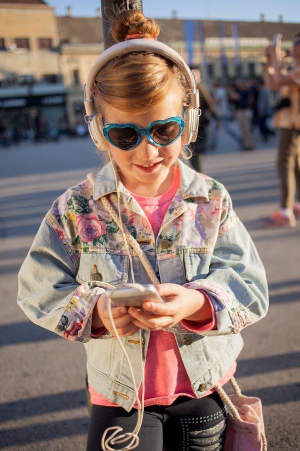 El niño feliz de la muchacha escucha la música de su smartphone fotos de archivo libres de regalías