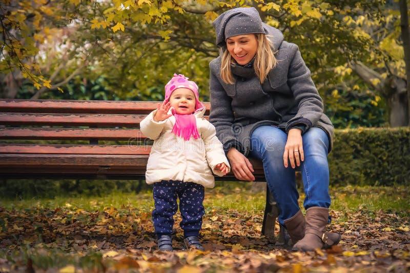 El niño feliz del bebé dice hola a la madre del otoño del parque fotos de archivo