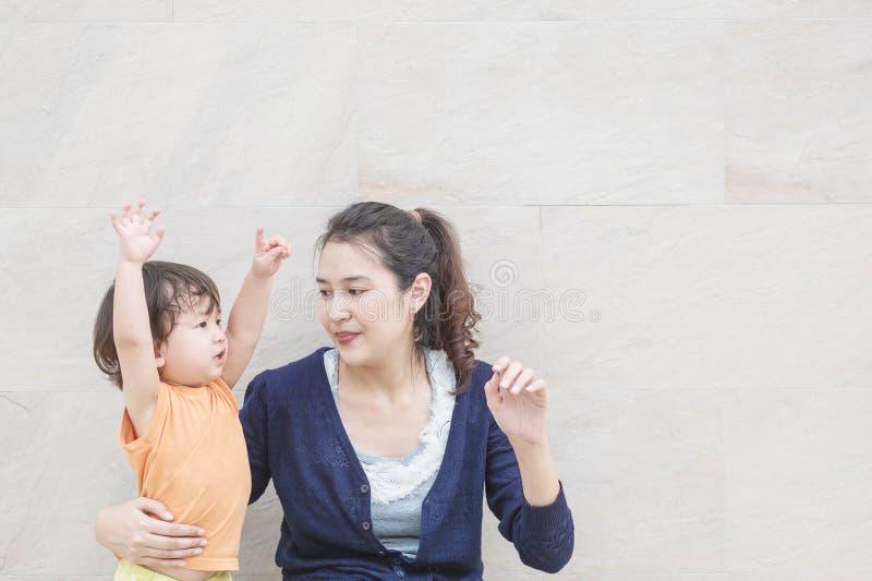 El niño feliz del primer cuenta una historia a su madre con excita el movimiento en el fondo texturizado de mármol de la pared de imagen de archivo libre de regalías