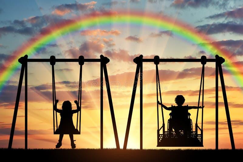El niño feliz es una persona discapacitada en una silla de ruedas que monta un oscilación adaptante al lado de un niño sano ju imagen de archivo libre de regalías