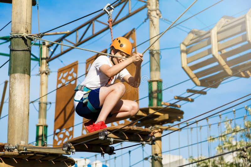 El niño feliz, escolar sano del adolescente en casco anaranjado disfruta de actividad en un parque de la cuerda de la aventura qu imagen de archivo