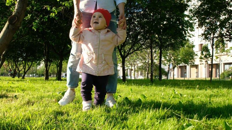 El niño feliz está aprendiendo caminar en el parque en la puesta del sol La madre ayuda al bebé a tomar las primeras medidas fotos de archivo libres de regalías
