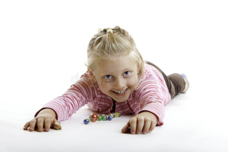 El niño feliz está mintiendo en el suelo con mármoles imagenes de archivo