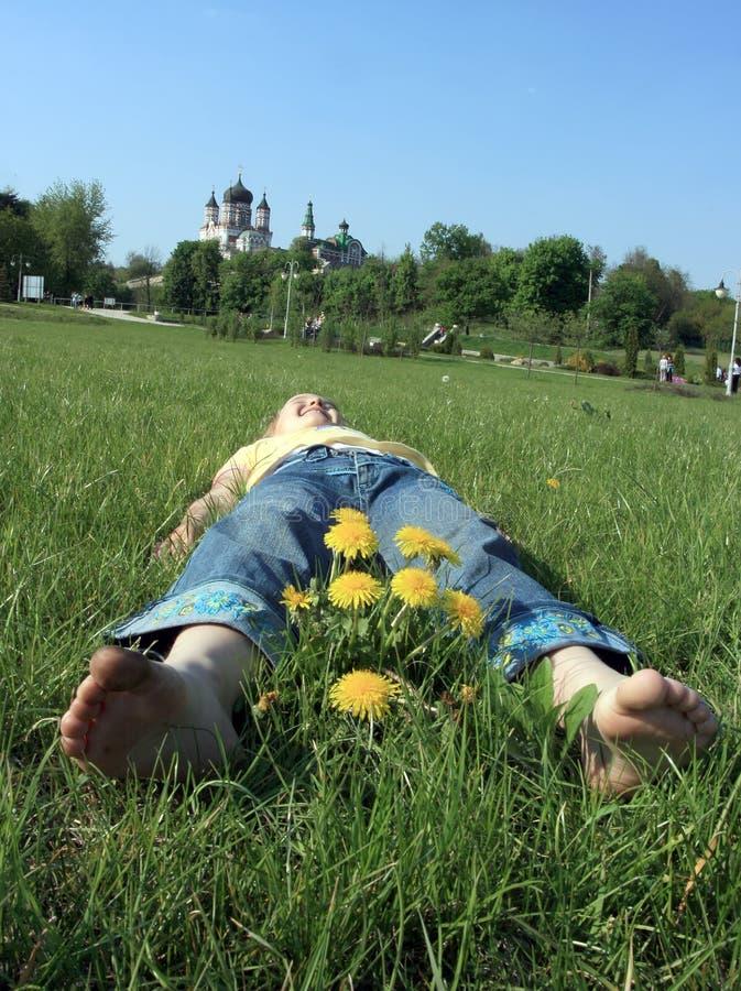 El niño feliz está mintiendo en hierba verde al aire libre en el parque imagenes de archivo