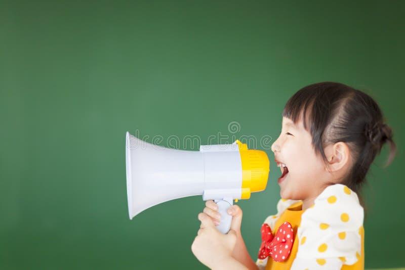 El niño feliz grita algo en el megáfono imagen de archivo
