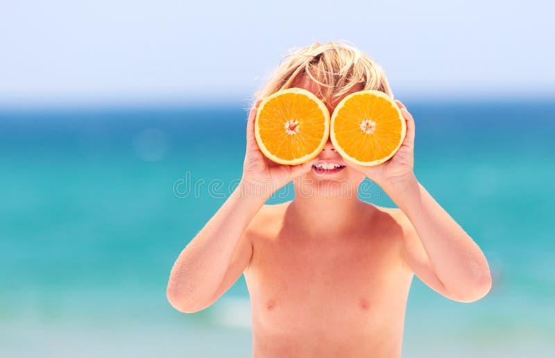 El niño feliz lindo, muchacho joven que muestra la naranja observa mientras que divirtiéndose en la playa en las vacaciones de ve fotografía de archivo libre de regalías
