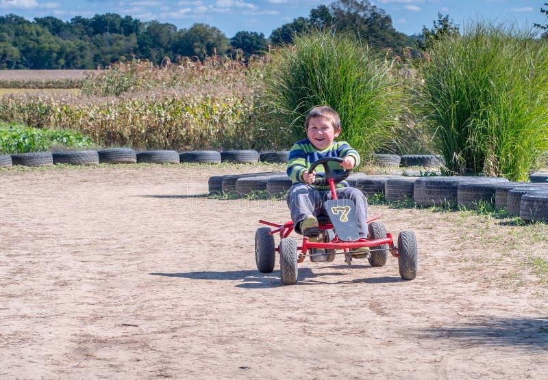 El niño feliz monta un coche del pedal alrededor de una pista foto de archivo