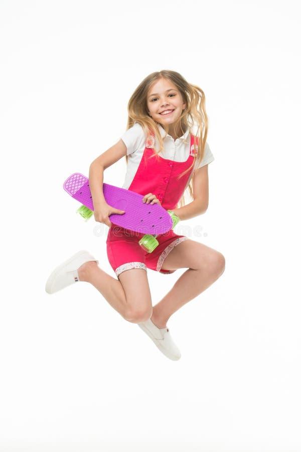 El niño feliz salta con el tablero del penique aislado en blanco Sonrisa del niño con el monopatín Diversión en el movimiento Sen imágenes de archivo libres de regalías