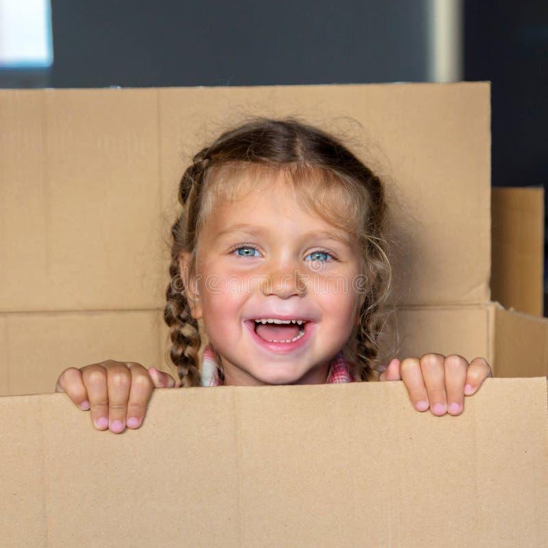 El niño feliz se divierte y goza el jugar de escondite foto de archivo