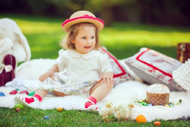 El niño feliz se sienta en un prado alrededor de la decoración de pascua imágenes de archivo libres de regalías