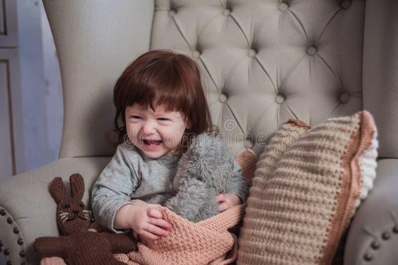 El niño feliz se sienta en una silla Risa feliz del bebé pelirrojo fotos de archivo