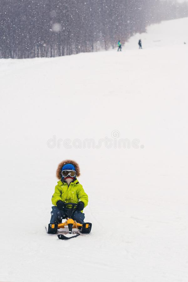 El niño feliz sledding en día de invierno nevoso Niño del niño que monta un trineo Días de fiesta de invierno Niñez feliz Vacacio fotos de archivo