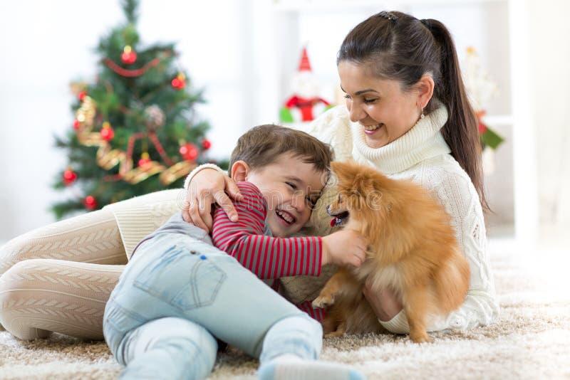 El niño feliz y su mamá están mintiendo en piso cerca del árbol de navidad y están abrazando el perro Están mirando el animal dom imagenes de archivo