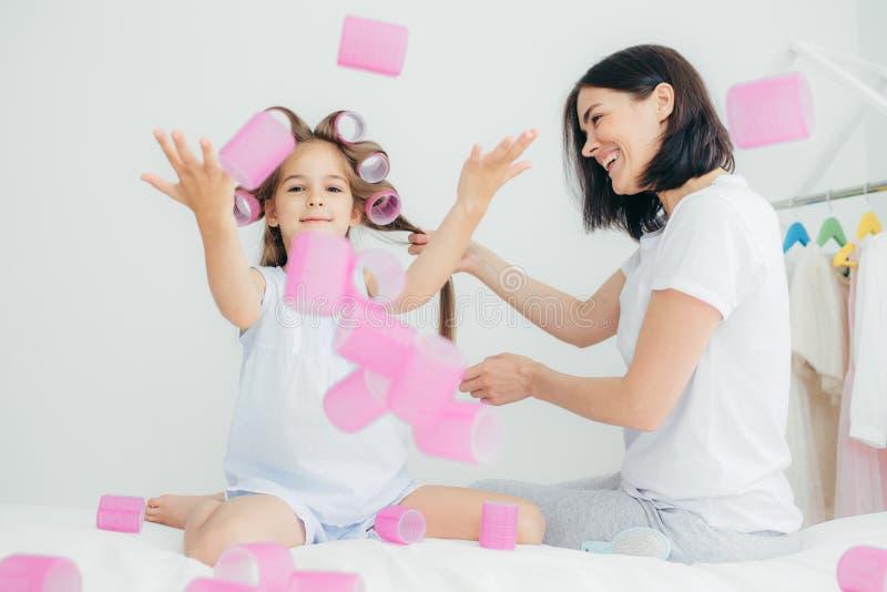 El niño femenino divertido lanza los bigudíes en aire, se divierte junto, su madre hace el peinado, lleva la ropa casual Vientos  fotografía de archivo libre de regalías