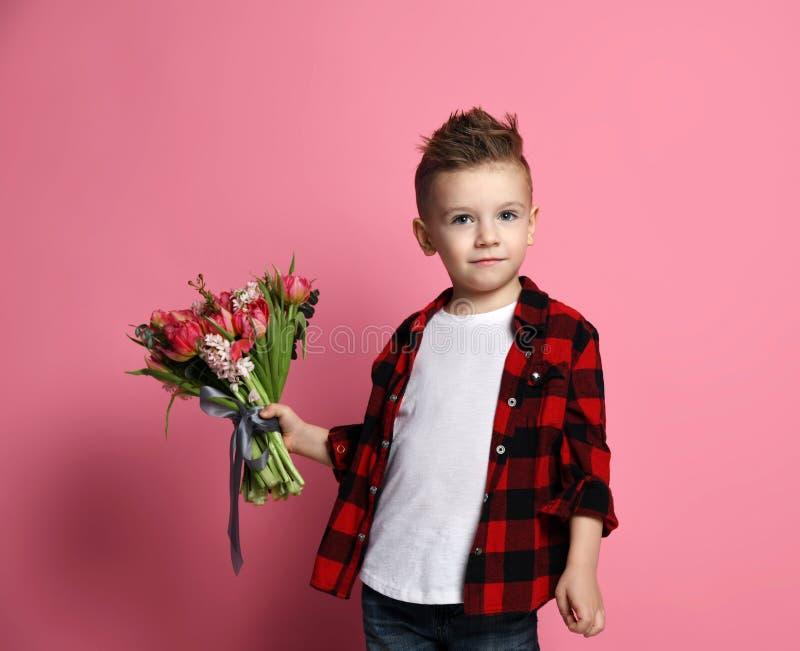 El niño fresco del niño pequeño en tejanos y camisa roja con un ramo grande de flores de la primavera espera o encuentra alguien fotografía de archivo