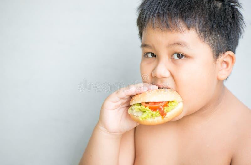 El niño gordo obeso del muchacho come la hamburguesa del pollo imagenes de archivo