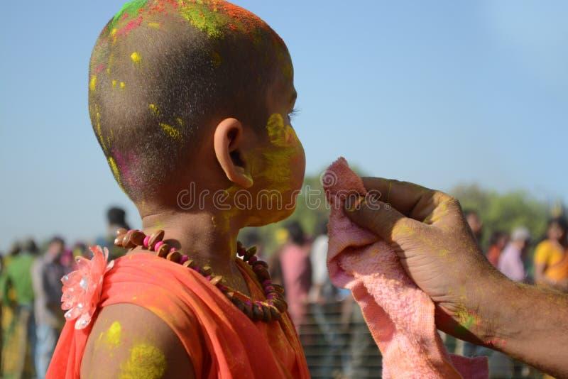 El niño gozó de Holi con su padre, su padre que limpiaba su cara el festival del color de la India fotos de archivo