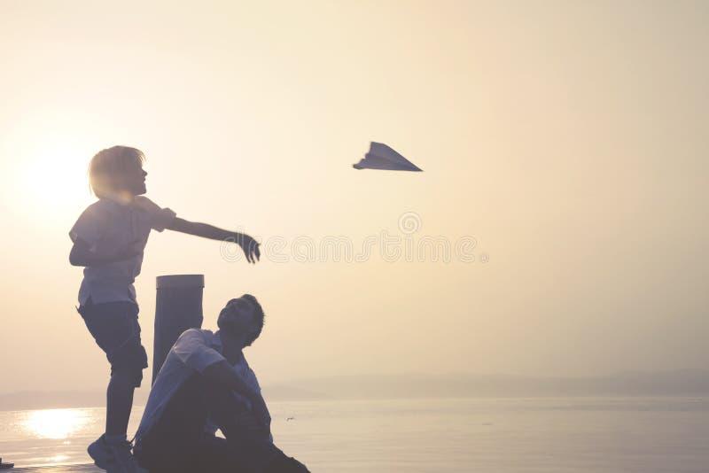 El niño hace mosca su aeroplano de papel imagenes de archivo