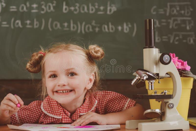 El niño hace el trabajo académico y de investigación en sala de clase Investigación de la niña con el microscopio en el laborator imagen de archivo