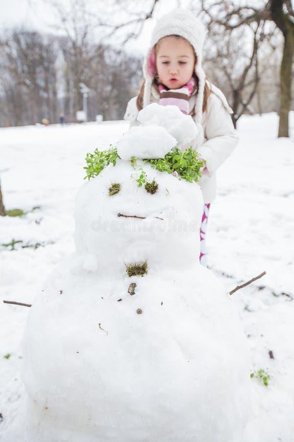 El niño hace un muñeco de nieve en el parque en el día de invierno foto de archivo libre de regalías