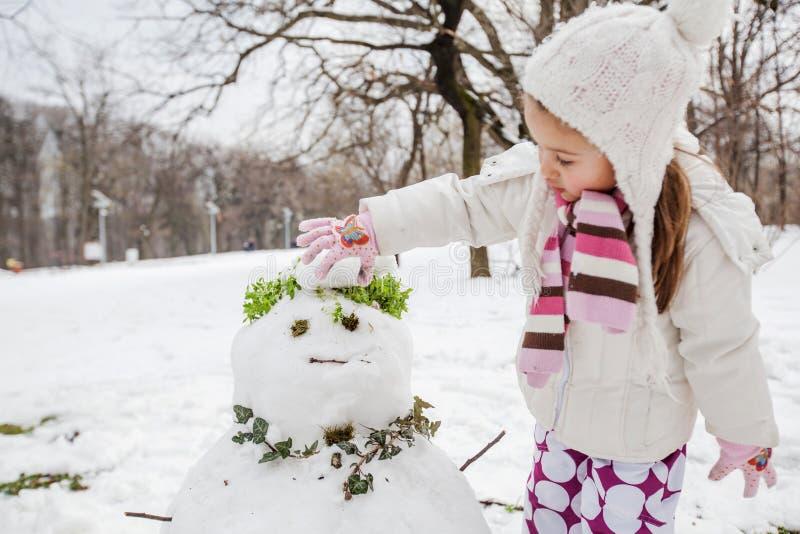 El niño hace un muñeco de nieve en el parque en el día de invierno foto de archivo