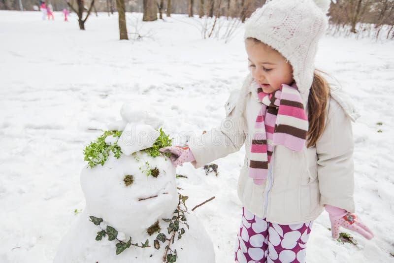 El niño hace un muñeco de nieve en el parque en el día de invierno fotografía de archivo libre de regalías