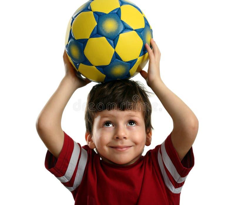 El niño hermoso sostiene un balón de fútbol sobre su cabeza foto de archivo libre de regalías