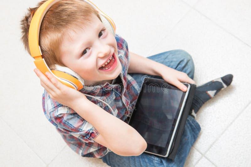 El niño joven es música que escucha con el auricular en la tableta fotos de archivo libres de regalías