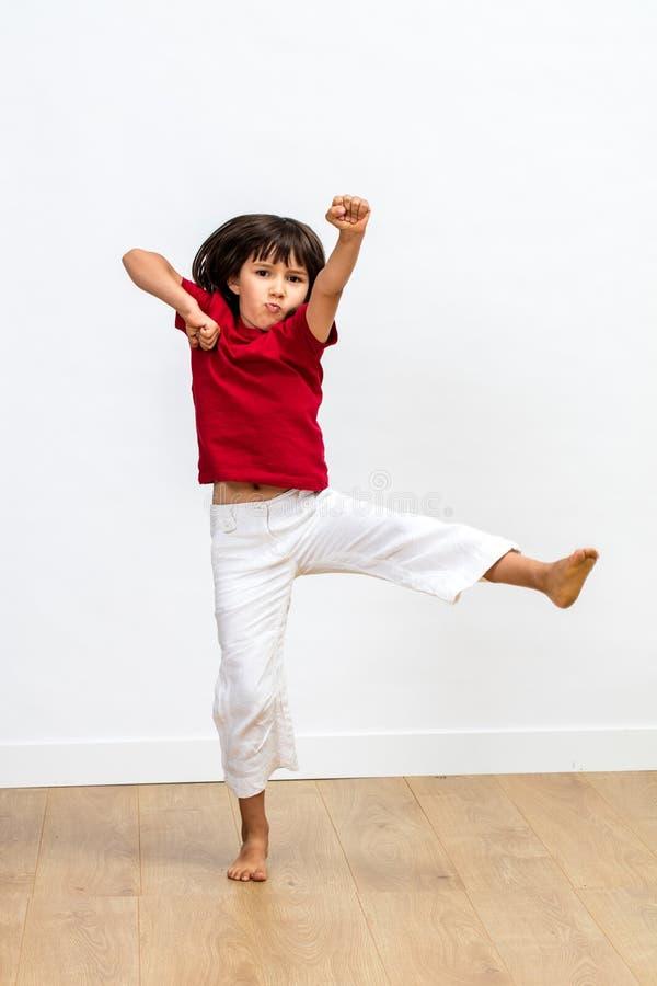 El niño joven que luchaba con los brazos aumentó el goce ejercitando arte marcial imagen de archivo