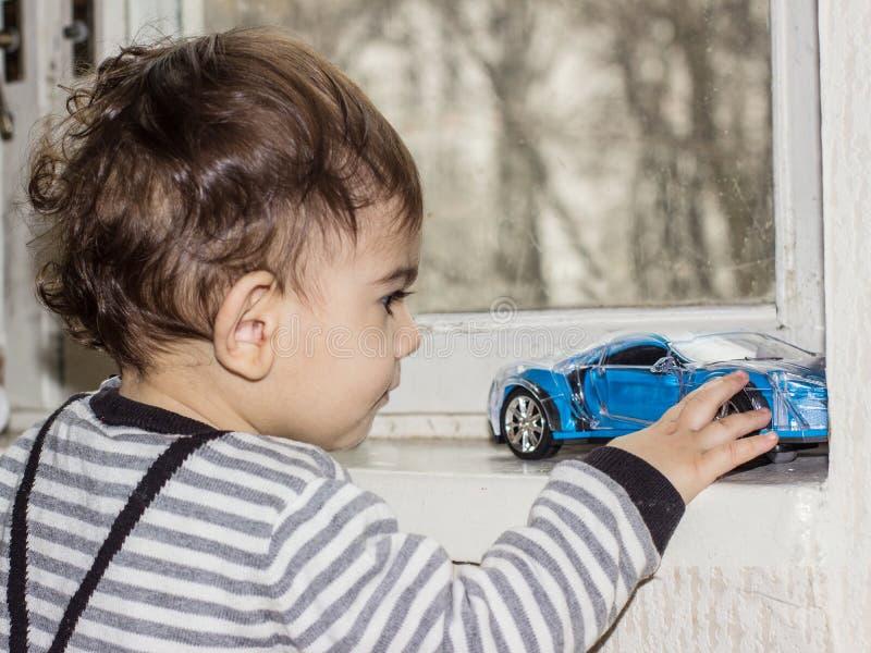 El ni?o juega con un coche del juguete Retrato emocional de un ni?o de un a?o imágenes de archivo libres de regalías