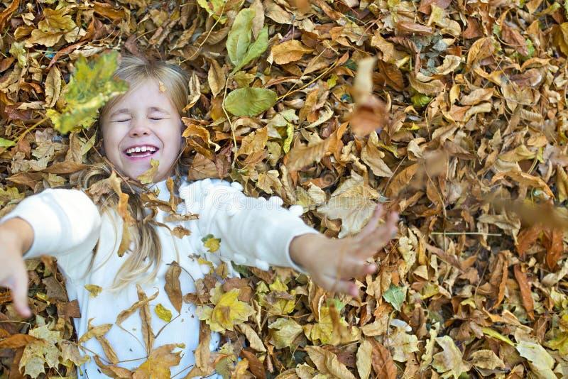 El niño juega en parque del otoño Niño que lanza las hojas amarillas y rojas Ni?a con el roble y la hoja de arce Follaje de ca?da fotografía de archivo
