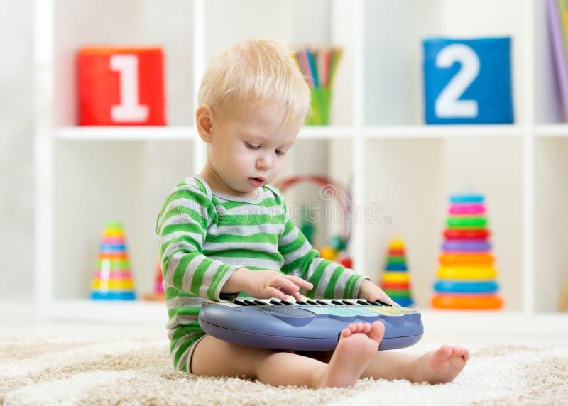 El niño juega el piano del juguete que se sienta en piso en cuarto de niños fotos de archivo