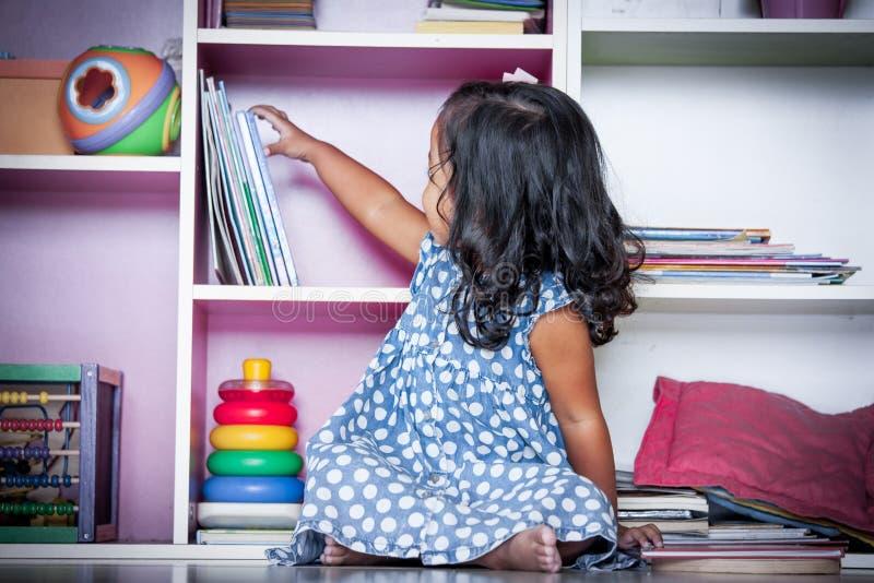 El niño leyó, niña linda que seleccionaba un libro en el estante fotografía de archivo libre de regalías